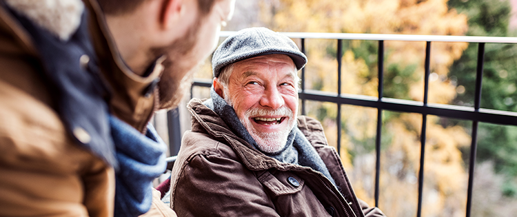 Older man laughing with his son outside