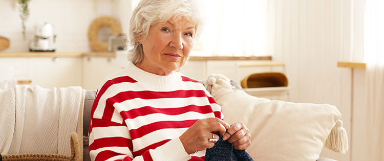 Senior woman knitting and smiling.