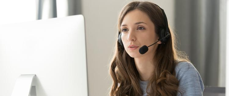 young woman with a headset on looking at computer