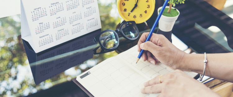 Person writing in planner with a blue pencil on a desk filled with a calendar, yellow clock, plant, and glasses.