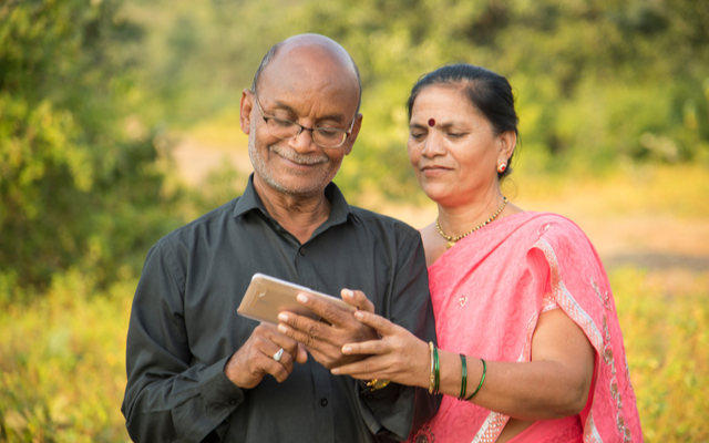 Older couple smiling at phone