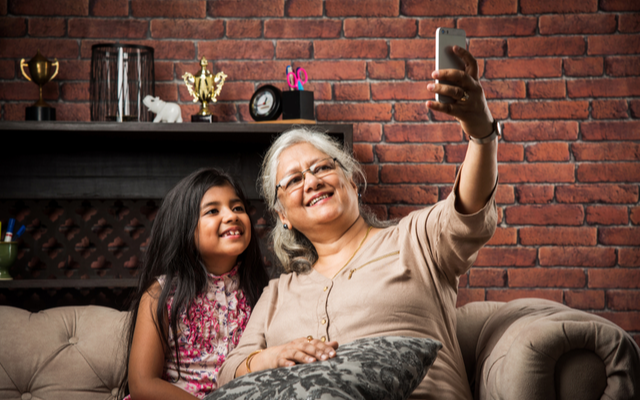 Senior woman taking a selfie with granddaughter