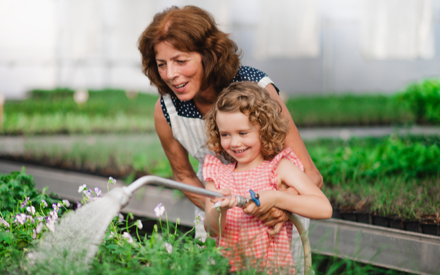 woman and young girl smiling and watering plants together.