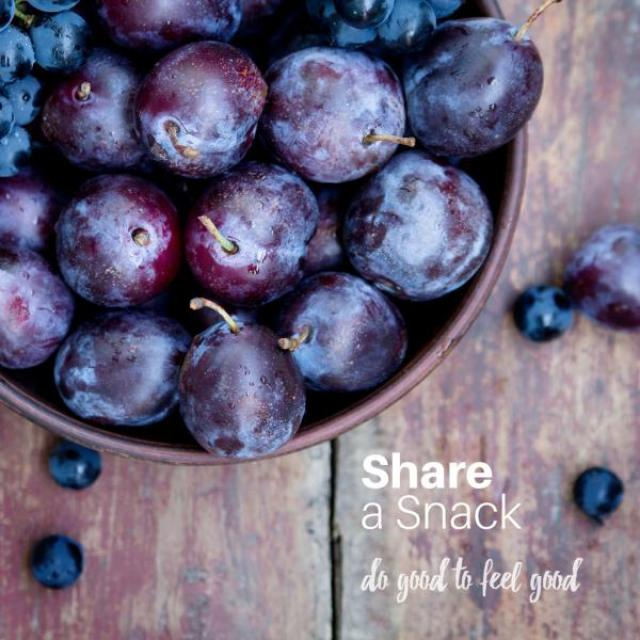 "A bowl of purple grapes sits on a wooden table. The text ""Share a snack. Do good to feel good."" is overlaid in the corner."