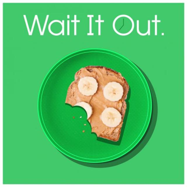 "Open-face peanut butter and banana sandwich with a few bites taken out of it on a plate. Text above it says ""Wait it Out."" The O of the word ""out"" has the hands of a clock inside it."